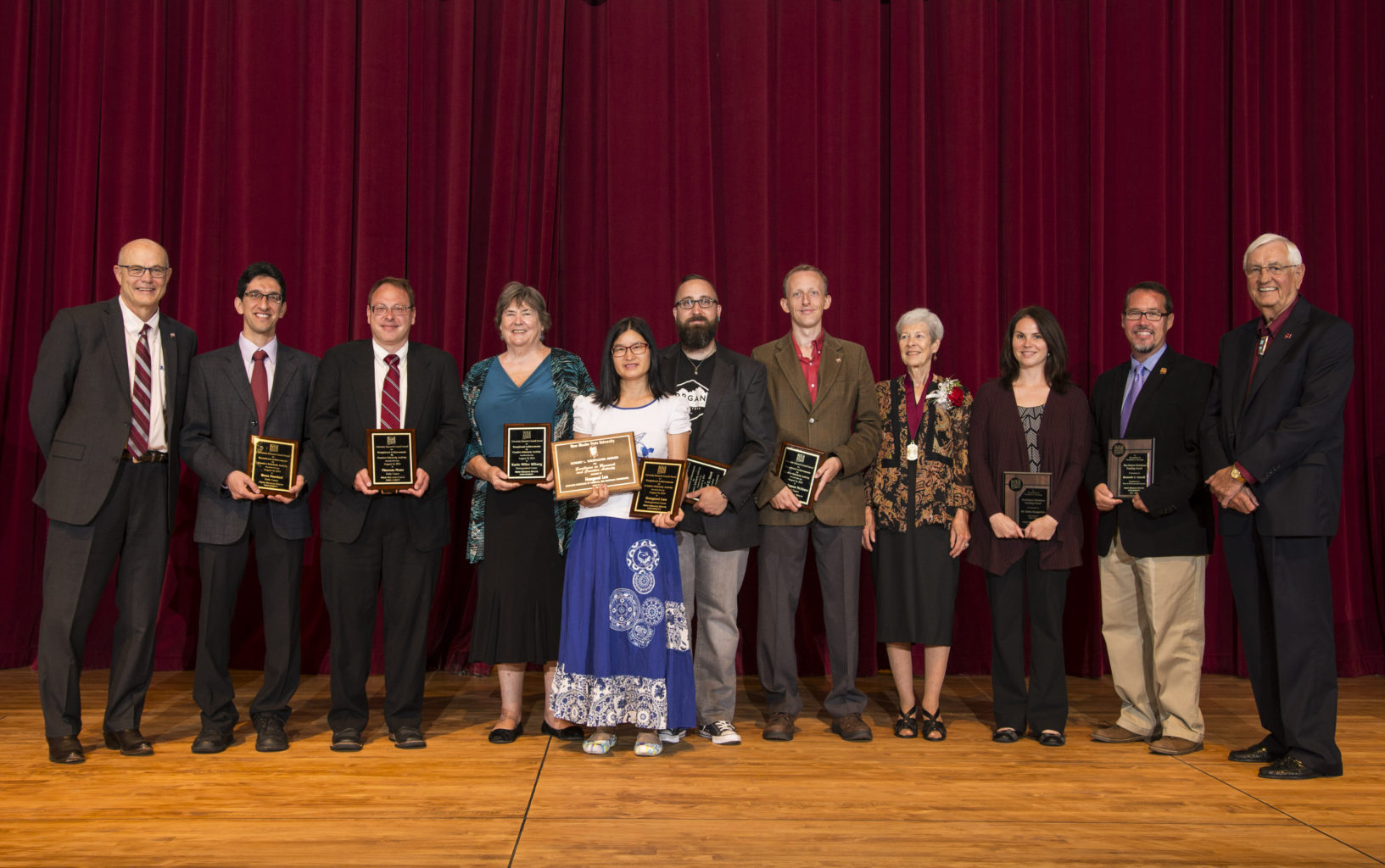 NMSU faculty award winners are joined by NMSU president Garrey Carruthers, far right, and provost Dan Howard, far left, for a group photo following the 2016 fall convocation ceremony at Atkinson Recital Hall. Awardees include, from left to right, Reza Foudazi, Tom Manz, Karin Wiburg, Hongmei Luo, Michael Hout, James McAteer, Karen Becklin, Erika Gergerich and Kenneth Carroll. (Photo by Andres Leighton) AUG16